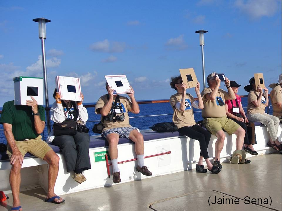A line of people with boxes & cardboard and welder's glass view the eclipse.